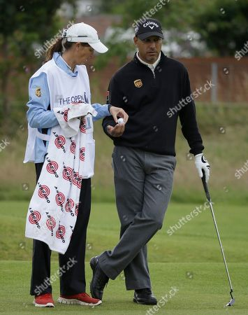 Jeev Milkha Singh of India has his ball cleaned by his caddie Janet Squire on the fourth green at Royal Lytham & St Annes golf club during the second round of the British Open Golf Championship, Lytham St Annes, England