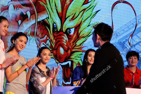 From left, former Olympic volleyball player, Zhao Ruirui, former Miss World Zhang Zilin, Chinese actresses Yao Chen, Fan Bingbing and former Olympic volleyball player Yang Hao watch managing director of Greater China, Colin Currie stepping on stage during a publicity event to show support for Chinese athletes ahead of the London Olympic Games in Beijing
