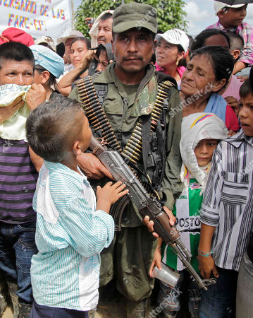A child looks up at a member of the Revolutionary Armed Forces of Colombia (FARC) during a ceremony for the rebel handover of a French journalist in San Isidro in southern Colombia, . French journalist Romeo Langlois, who was taken by rebels of the Revolutionary Armed Forces of Colombia (FARC) on April 28 when they attacked troops he was accompanying on a cocaine-lab eradication mission, was handed over by the rebels to a delegation in San Isidro on Wednesday