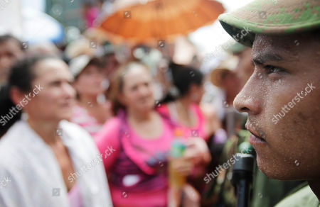 Sweat beads on the face of a rebel of the Revolutionary Armed Forces of Colombia (FARC) during a ceremony for the rebel handover of a French journalist in San Isidro in southern Colombia, . French journalist Romeo Langlois, who was taken by rebels on April 28 when they attacked troops he was accompanying on a cocaine-lab eradication mission, was handed over by the FARC to a delegation that included a French diplomat in San Isidro