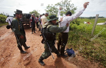 Rebels of the Revolutionary Armed Forces of Colombia, FARC, frisk a man at a roadblock in San Isidro, southern Colombia, . Journalist Romeo Langlois, who was taken by rebels on April 28 when they attacked troops he was accompanying on a cocaine-lab eradication mission, is expected to be handed over by the rebels to a delegation that includes a French diplomat in San Isidro