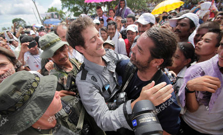 French journalist Romeo Langlois, center left, embraces fellow journalist Carlos Villalon, from Chile, in San Isidro in southern Colombia, . Langlois, who was taken by rebels of the Revolutionary Armed Forces of Colombia (FARC) on April 28 when they attacked troops he was accompanying on a cocaine-lab eradication mission, was handed over by the rebels to a delegation that included a French diplomat
