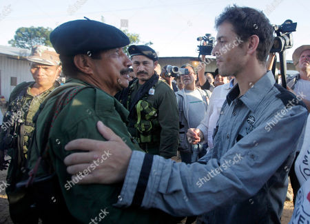 French Journalist Romeo Langlois, left, embraces a leader of the Revolutionary Armed Forces of Colombia, FARC, known as Jairo in San Isidro, southern Colombia, . Langlois, who was taken by rebels on April 28 when they attacked troops he was accompanying on a cocaine-lab eradication mission, was handed over by the rebels to a delegation that included a French diplomat