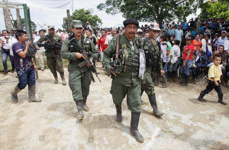Rebel leader of the Revolutionary Armed Forces of Colombia, FARC, known as Jairo, center, walks in San Isidro, southern Colombia, . Journalist Romeo Langlois, who was taken by rebels on April 28 when they attacked troops he was accompanying on a cocaine-lab eradication mission, is expected to be handed over by the rebels to a delegation that includes a French diplomat in San Isidro
