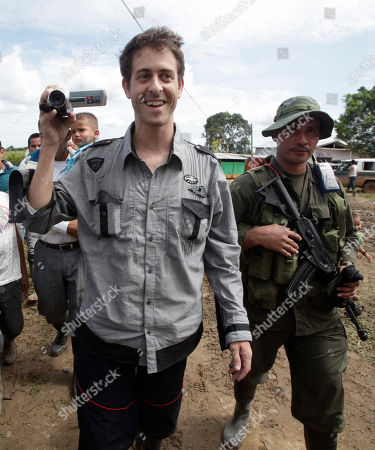 French journalist Romeo Langlois, left, films as he arrives escorted by rebels of the Revolutionary Armed Forces of Colombia (FARC) to San Isidro in southern Colombia, . Langlois, who was taken by rebels on April 28 when they attacked troops he was accompanying on a cocaine-lab eradication mission, was handed over by the rebels to a delegation that included a French diplomat in San Isidro