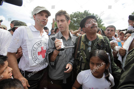 A Red Cross delegate, left, released French journalist Romeo Langlois, center, and a rebel stand together in San Isidro in southern Colombia, . French journalist Romeo Langlois, who was taken by rebels on April 28 when they attacked troops he was accompanying on a cocaine-lab eradication mission, was handed over by the FARC to a delegation that included a French diplomat in San Isidro