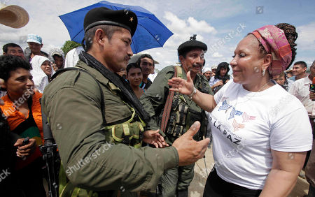 Former Senator Piedad Cordoba, right, greets a rebel of the Revolutionary Armed Forces of Colombia (FARC) in San Isidro in southern Colombia, . French journalist Romeo Langlois, who was taken by rebels on April 28 when they attacked troops he was accompanying on a cocaine-lab eradication mission, was handed over by the rebels to a delegation that included Cordoba and a French diplomat in San Isidro