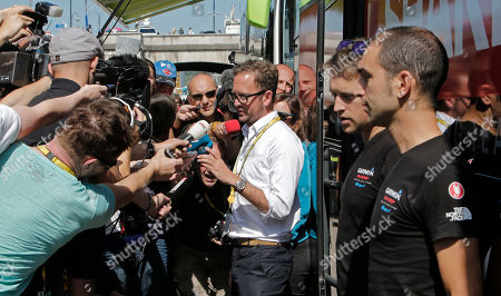"Jonathan Vaughters, a director of Garmin-Sharp, center in white shirt, denied that any of the cycling team's riders have been banned for six months by the U.S. Anti-Doping Agency as part of its doping probe into seven-time Tour de France winner Lance Armstrong during an improvised press conference outside the team bus prior to the start of the fifth stage of the Tour de France cycling race over 196.5 kilometers (122 miles) with start in Rouen and finish in Saint-Quentin, France, . Vaughters said Thursday that a Dutch media report about six-month bans is ""completely untrue."" Dutch newspaper De Telegraaf reported Wednesday that Vaughters and four other former Armstrong teammates have been given six-month bans to begin in late September. De Telegraaf cites unnamed ""well-informed sources"" in its report that Vaughters, George Hincapie, Levi Leipheimer, David Zabriskie and Christian Vande Velde received the bans after admitting to doping and agreeing to give evidence against Armstrong"