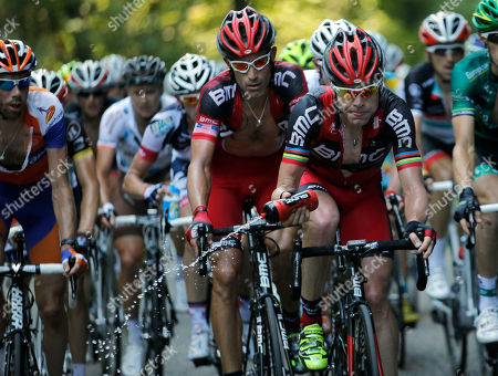 Cadel Evans of Australia empties his drinking bottle as he rides with teammate George Hincapie of the US, center, and Bram Tankink of the Netherlands, far left, during the 10th stage of the Tour de France cycling race over 194.5 kilometers (120.9 miles) with start in Macon and finish in Bellegarde-sur-Valserine, France