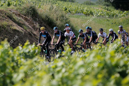 Overall leader Bradley Wiggins of Britain, Christopher Froome of Britain, and Edvald Boasson Hagen of Norway, from left, ride with Sky teammates as the pass Beaujolais vineyards during a training on he rest day of the Tour de France cycling race at the team hotel in Quincie-en-Beaujolais, near Macon, France