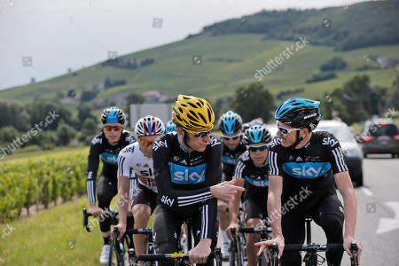 Overall leader Bradley Wiggins of Britain, center left, Christopher Froome of Britain, right, and Edvald Boasson Hagen of Norway, second left, ride with Sky teammates through Beaujolais vineyards during a training on he rest day of the Tour de France cycling race in Quincie-en-Beaujolais, near Macon, France