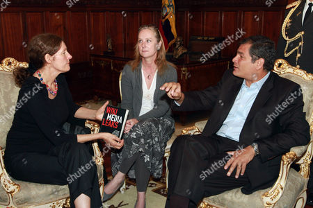Christine Assange, left, the mother of WikiLeaks founder Julian Assange, holds a copy of a book by Martin Becerra and Sebastian Lacunza presented to her by Ecuador's President Rafael Correa, right, at their meeting in Quito, Ecuador, . Christine Assange is in Ecuador to meet with officials about her son's political asylum request. Ecuadorean officials have said they will not announce a decision until after the London Olympic Games end in mid-August. The 40-year-old Australian has been holed up inside the Ecuadorian Embassy in London since applying for political asylum on June 19. Woman seated at center is a translator