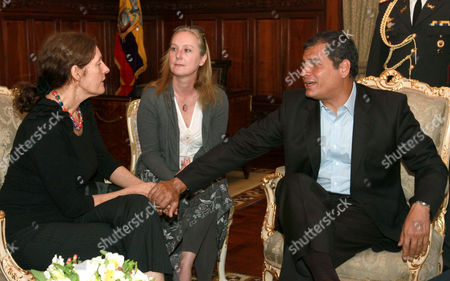Ecuador's President Rafael Correa holds the hands of Christine Assange, the mother of WikiLeaks founder Julian Assange, during their meeting in Quito, Ecuador, . Christine Assange is in Ecuador to meet with officials about her son's political asylum request. Ecuadorean officials have said they will not announce a decision until after the London Olympic Games end in mid-August. The 40-year-old Australian has been holed up inside the Ecuadorian Embassy in London since applying for political asylum on June 19. The woman seated between Assange and Correa is a translator