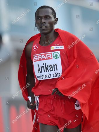 Turkey's Polat Kemboi Arikan carries a flag ater finishing third in the Men's 5000 meter final at the European Athletics Championships in Helsinki, Finland