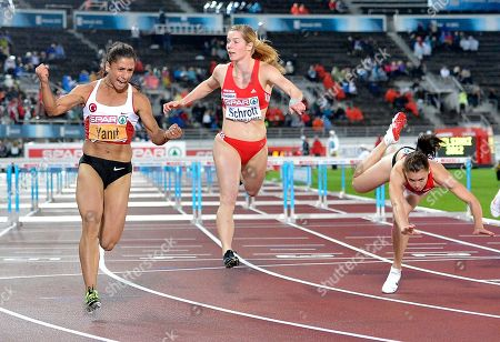 Turkey's Nevin Yanit, left, crosses the finish line to win the Women's 100 meter Hurdles final at the European Athletics Championships in Helsinki, Finland, . At right falls Belarus' Alina Talay who won silver. Center Austrian Beate Schrott