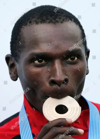 Turkey's Polat Kemboi Arikan bites the bronze medal he won in the Men's 5000 meter final at the European Athletics Championships in Helsinki, Finland