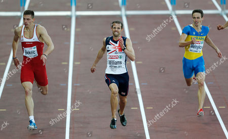 Britain's Rhys Williams, center, runs to win the Men's 400 meter Hurdles final at the European Athletics Championships in Helsinki, Finland, . Right is Ukraine's Stanislav Melnykov who came in third, left is Serbia's Emir Bekric who took silver