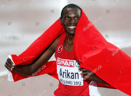 Turkey's Polat Kemboi Arikan poses with the national flag after winning the Men's 10000 meter final at the European Athletics Championships in Helsinki, Finland