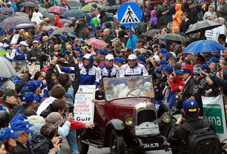 From left to right, Toyota drivers Kazuki Nakajima of Japan, Nicolas Lapierre of France and Alexander Wurz of Germany wave supporters during a parade on the eve of the 80th 24-hours Le Mans endurance race in Le Mans, western France