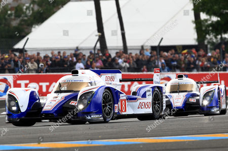 The both Toyota TS030 Hybrid No8 driven by Stephane Sarrazin of France, left, and No7 driven by Alexander Wurz of Germany, right, steer their car in a curve during the 80th 24-hour Le Mans endurance race, in Le Mans, western France