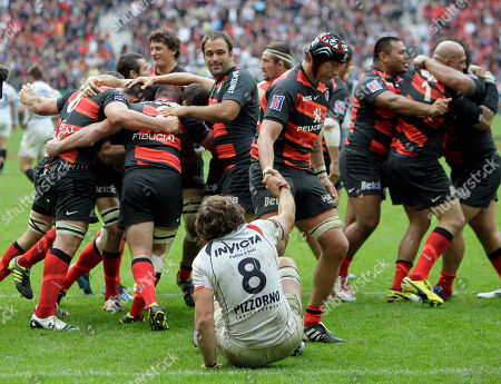 Stock Image of Patricio Albacete, Juan Martin Fernandez Toulouse's Patricio Albacete, center top, helps Toulon's Juan Martin Fernandez as Toulouse team in background celebrate their victory over Toulon during their Top 14 final rugby match at Stade de France stadium in Saint Denis, north of Paris, France, . Toulouse won the final by 18-12