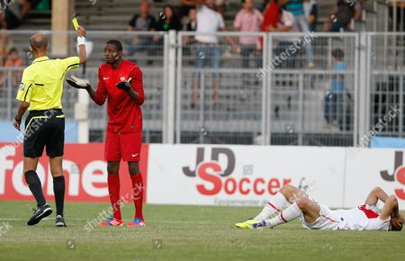 M. Mabrouk, Abdoulaye Diallo, Erkan Kas Referee M. Mabrouk of Morocco, left, gives a yellow card at France's goalkeeper Abdoulaye Diallo, center, as Turkey's Erkan Kas, right, is lying on the field, during their semi final match in the Under-21 Toulon soccer Tournament, in Avignon, southern France