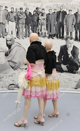 Performers 'Eva and Adele',from left, in front of an art tapestry to the Afghanistan theme 'Of what is, that it is; of what is not, that is it not' (2012) of British based artist Goshka Macuga during the press preview of the dOCUMENTA (13 ) in Kassel, Germany, . For 100 days, over 150 artists from 55 countries and other participants from around the world will gather and present their works. The 13th edition of the 'dOCUMENTA' international contemporary arts exhibition, which is held once every five years, will be open to public from June 9 until Sept. 16, 2012