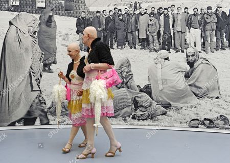 Performers 'Eva and Adele' (from left) walk in front of an art tapestry to the Afghanistan theme 'Of what is, that it is; of what is not, that is it not' (2012) of British based artist Goshka Macuga during the press preview of the dOCUMENTA (13)in Kassel, Germany, . For 100 days, over 150 artists from 55 countries and other participants from around the world will gather and present their works. The 13th edition of the 'dOCUMENTA' international contemporary arts exhibition, which is held once every five years, will be open to public from June 9 until Sept. 16, 2012