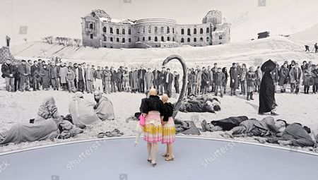 Performers 'Eva and Adele' walk in front of an art tapestry to the Afghanistan theme 'Of what is, that it is; of what is not, that is it not' (2012) of British based artist Goshka Macuga during the press preview of the dOCUMENTA (13) in Kassel, Germany, . For 100 days, over 150 artists from 55 countries and other participants from around the world will gather and present their works. The 13th edition of the 'dOCUMENTA' international contemporary arts exhibition, which is held once every five years, will be open to public from June 9 until Sept. 16, 2012