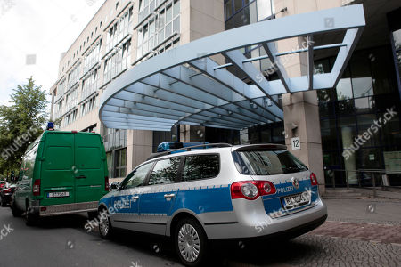Police cars stand in front of the central police detention facility of Berlin where Luka Rocco Magnotta is being in Berlin, Germany, . Luka Magnotta, 29, a Canadian porn actor suspected of murdering and dismembering a Chinese was arrested on Monday at an Internet cafe in a working-class district of the German capital, where he had been reading media coverage of himself. A cafe employee recognized Magnotta from a newspaper photo and flagged down a police car