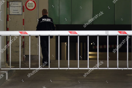 A police officer walks inside the car gateway of the central police detention facility of Berlin where Luka Rocco Magnotta is being held in Berlin, Germany, . Luka Magnotta, 29, a Canadian porn actor suspected of murdering and dismembering a Chinese was arrested on Monday at an Internet cafe in a working-class district of the German capital, where he had been reading media coverage of himself. A cafe employee recognized Magnotta from a newspaper photo and flagged down a police car. The white child left reads 'Centrap Police Detention