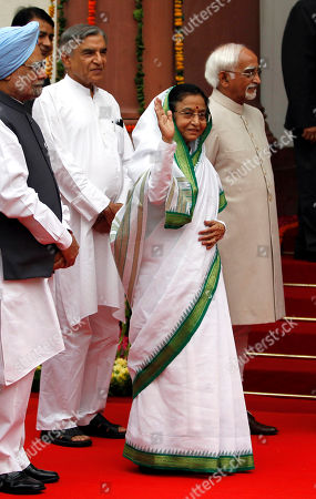 Pratibha Patil, Manmohan Singh, Hamid Ansari Outgoing Indian President Pratibha Patil, center, waves to the media, as Indian Prime Minister Manmohan Singh, left, and Vice President Hamid Ansari, right, watch as they enter the Central Hall of the Indian Parliament in New Delhi, India, . Patil addressed her farewell speech at the Parliament, Monday