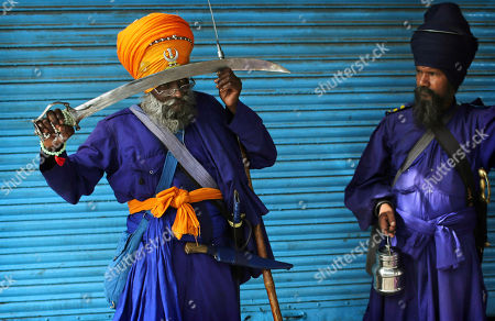 Indian Sikh Nihang holds his sword against his head to pray while his fellow man looks on near the Sheesh Ganj Gurudwara Sikh temple in New Delhi, India, . They are members of the Nihang Order, an armed group that played a crucial role in Sikh history