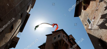 """An Italian national flag hangs between two buildings in the Garbatella district in Rome, in this picture taken . Woody Allen's latest cinematographic effort """"To Rome with Love"""" casts big names like Penelope Cruz, Alec Baldwin, Judy Davis and Allen himself, but there is one exceptional star: the Eternal City. Woody Allen's Rome is beautiful, clean and sunny, a city shining in pristine beauty. Allen omits Rome's current societal problems, degradation and economic stagnation to show the city in all its charm. To show his affection for the city, Allen tries to bring his postcard portrayal to life by going beyond the touristic and most famous locations, to capture the unconventional and popular atmosphere of neighborhoods like Sant'Angelo, Garbatella and Rione Monti"""