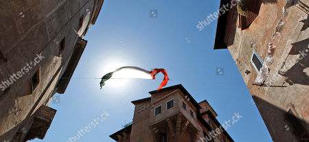 """In this picture taken an Italian national flag hangs between two buildings in the Garbatella district in Rome. Woody Allen's latest cinematographic effort """"To Rome with Love"""" casts big names like Penelope Cruz, Alec Baldwin, Judy Davis and Allen himself, but there is one exceptional star: the Eternal City. Woody Allen's Rome is beautiful, clean and sunny, a city shining in pristine beauty. Allen omits Rome's current societal problems, degradation and economic stagnation to show the city in all its charm. To show his affection for the city, Allen tries to bring his postcard portrayal to life by going beyond the touristic and most famous locations, to capture the unconventional and popular atmosphere of neighborhoods like Sant'Angelo, Garbatella and Rione Monti"""