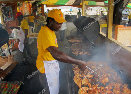 "Ian Marshall cooks the Jamaican specialty of ""pan chicken"" at a food stall set up on the grounds of the island's national stadium in Kingston, Jamaica, . Across Jamaica, islanders are marking the Caribbean island's 50th anniversary of independence from Britain by donning the national colors of gold, green and black and paying tribute to prominent islanders like black nationalist leader Marcus Garvey, reggae superstar Bob Marley and Olympic sprinting champion Usain Bolt"