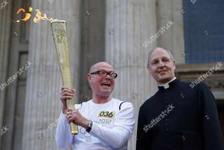 Torchbearer John Elbrow holds the Olympic Flame as he poses for pictures with David Ison, Dean of St. Paul's Cathedral, in central London, ahead of the 2012 Summer Olympics, . The Olympic Flame was carried around England in a relay of torchbearers to make its way to the opening ceremony on Friday