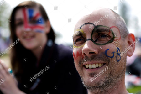 James Dutton of London and his daughter Kattie Dutton, 16, watch a broadcast of an Olympic tennis match on a large screen at Park Live inside Olympic Park during the 2012 Summer Olympics, in London