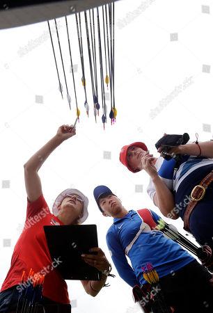 Khatuna Lorig, Tan Ya-Ting, Naomi Folkard From left, United State's Khatuna Lorig, Taiwan's Tan Ya-Ting and Britain's Naomi Folkard tally their scores during an individual ranking round at the 2012 Summer Olympics, in London