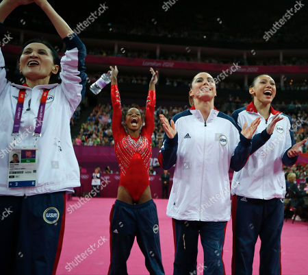 U.S. coach Jenny Zhang, left, celebrates with gymnasts, left to right, Gabrielle Douglas, McKayla Maroney and Kyla Ross as they look at the score of a team member's performance during the Artistic Gymnastics women's team final at the 2012 Summer Olympics, in London