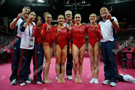 U.S. gymnasts, left to right wearing red, Gabrielle Douglas, McKayla Maroney, Alexandra Raisman, Jordyn Wieber and Kyla Ross celebrate with coaches Jenny Zhang, front left, Mihai Brestyan, back left, John Geddert, center, and Liang Chow, right, after their team won the gold medal for the Artistic Gymnastics women's team final at the 2012 Summer Olympics, in London