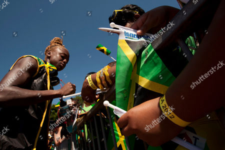 Stock Photo of Jamaica runner Dominique Blake, left, signs autographs during an open training session for the 2012 London Summer Olympics in Birmingham, England