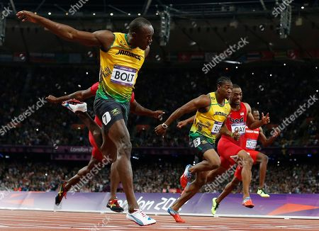 Jamaica's Usain Bolt, foreground left, goes to cross the finish line ahead of Jamaica's Yohan Blake, third from right, United States' Tyson Gay, second from right, and Trinidad's Richard Thompson in the men's 100-meters final during the athletics in the Olympic Stadium at the 2012 Summer Olympics, London