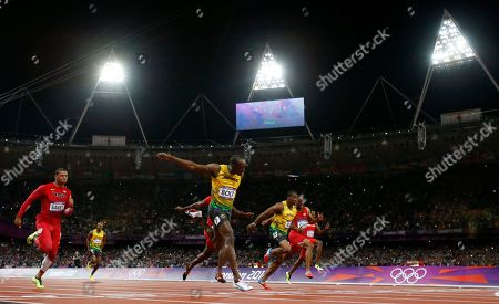 Jamaica's Usain Bolt, third from left, crosses the finish line to win gold ahead of United State's Ryan Bailey, left, Jamaica's Yohan Blake, third from right, United States' Tyson Gay, second from right, and Trinidad's Richard Thompson in the men's 100-meter final during the athletics in the Olympic Stadium at the 2012 Summer Olympics, London