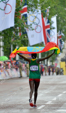 Ethiopia's Tiki Gelana celebrates with her country's flag after winning gold in the women's marathon at the 2012 Summer Olympics, in London