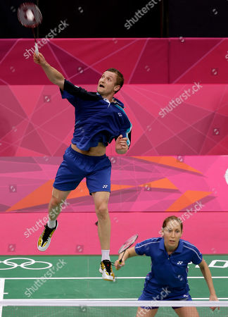 Russia's Alexandr Nikolaenko, rear, returns the shuttlecock as teammate Valeria Sorokina looks on while playing against Britain's Chris Adcock and Imogen Bankier in a mixed doubles badminton match at the 2012 Summer Olympics, in London