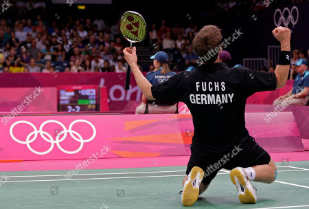 Germany's Michael Fuchs celebrates after he and teammate Birgit Michels beat Chris Adcock and Imogen Bankier of Great Britain during a mixed doubles badminton match at the 2012 Summer Olympics, in London