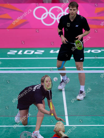 Germany's Birgit Michels, right, and Michael Fuchs, play against Britain's Chris Adcock, unseen, and Imogen Bankier, foreground, at a mixed doubles badminton match of the 2012 Summer Olympics, in London