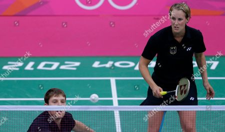 Germany's Birgit Michels, left, and Michael Fuchs, play against Britain's Chris Adcock and Imogen Bankier, unseen, at a mixed doubles badminton match of the 2012 Summer Olympics, in London