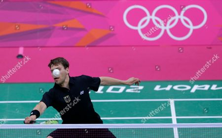 Germany's Michael Fuchs plays against Britain's Chris Adcock and Imogen Bankier, unseen, at a mixed doubles badminton match of the 2012 Summer Olympics, in London. Michels' partner, Birgit Michels, is also unseen